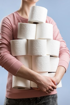 Vista frontal da mulher segurando vários rolos de papel higiênico