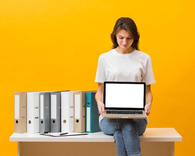 Vista frontal da mulher sentada na mesa e segurando laptop