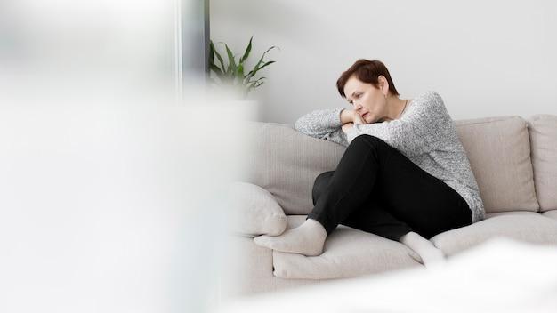 Vista frontal da mulher sentada no sofá
