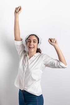 Vista frontal da mulher sorridente com fones de ouvido dançando