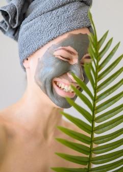Vista frontal da mulher sorridente com máscara facial em casa