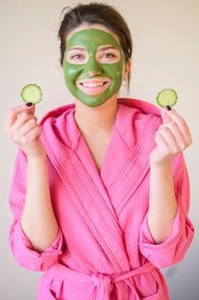 Vista frontal da mulher sorridente com máscara facial segurando fatias de pepino