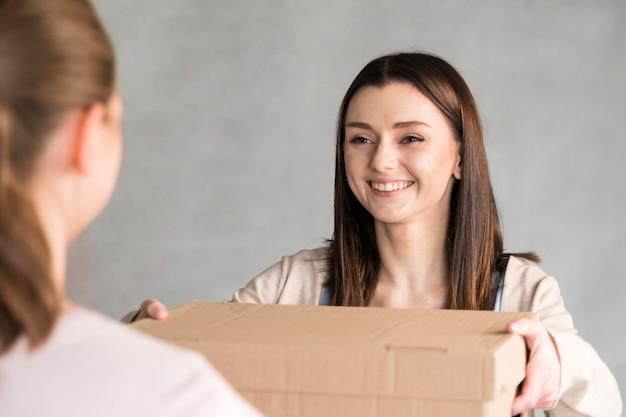 Vista frontal da mulher sorridente, entregando a caixa de papelão para o cliente