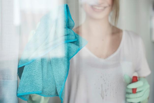 Vista frontal da mulher sorridente, limpando a janela