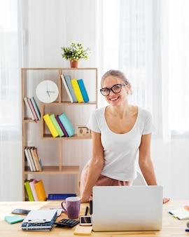 Vista frontal da mulher sorridente na mesa trabalhando em casa