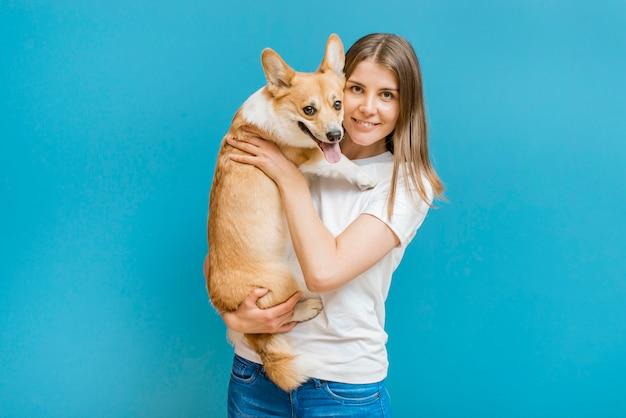Vista frontal da mulher sorridente posando com seu cachorro