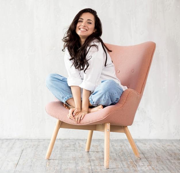 Vista frontal da mulher sorridente posando na cadeira