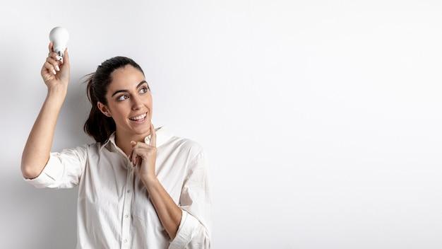 Vista frontal da mulher sorridente segurando a lâmpada acima da cabeça