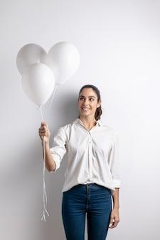 Vista frontal da mulher sorridente segurando balões
