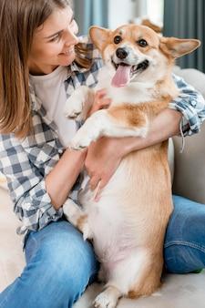 Vista frontal da mulher sorridente segurando cachorro