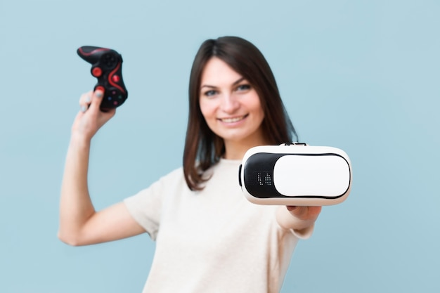 Vista frontal da mulher sorridente segurando fone de ouvido de realidade virtual