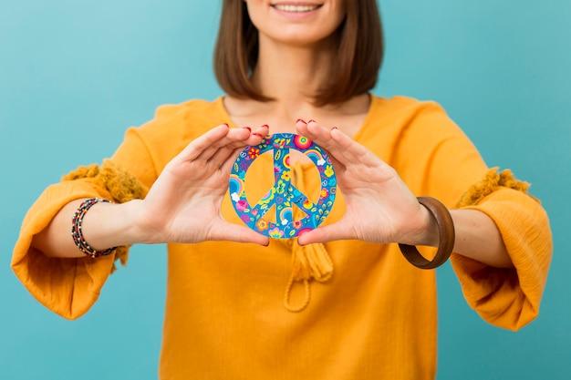 Vista frontal da mulher sorridente segurando sinal de paz