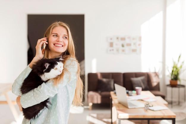 Vista frontal da mulher sorridente, trabalhando em casa, mantendo o gato