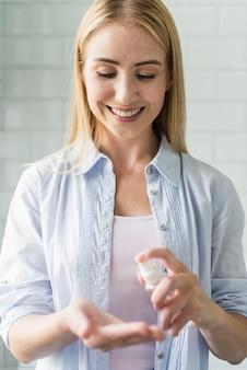 Vista frontal da mulher sorridente usando desinfetante para as mãos