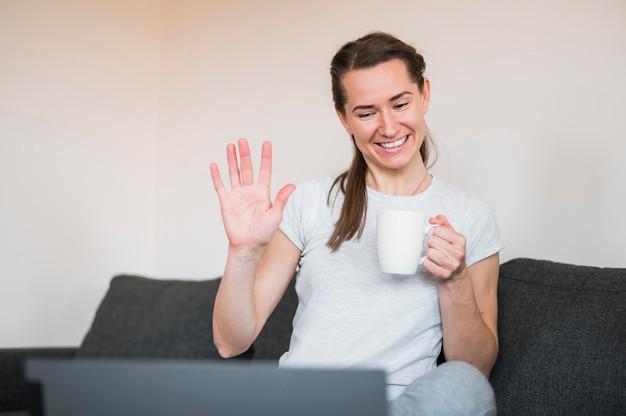 Vista frontal da mulher tendo uma chamada de vídeo