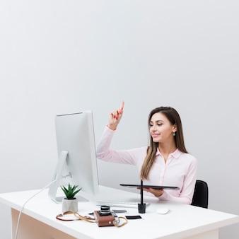 Vista frontal da mulher tendo uma ideia enquanto trabalhava na mesa dela