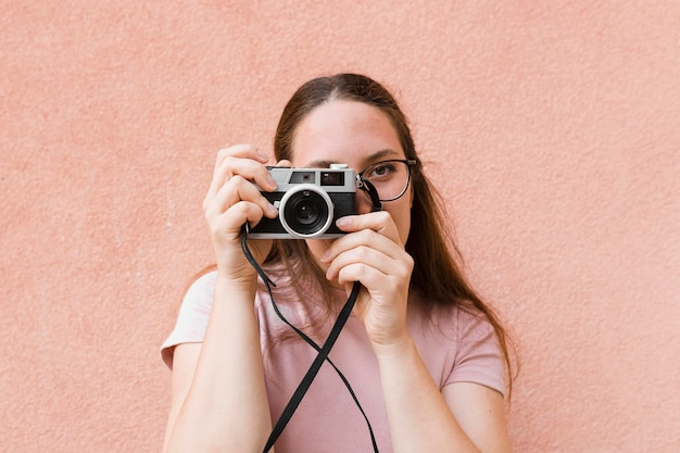 Vista frontal da mulher tirando uma foto com a câmera