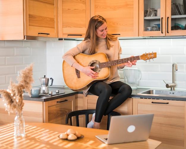 Vista frontal da mulher tocando violão