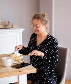 Vista frontal da mulher tomando café da manhã