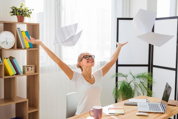 Vista frontal da mulher trabalhando em casa e jogando papéis no ar