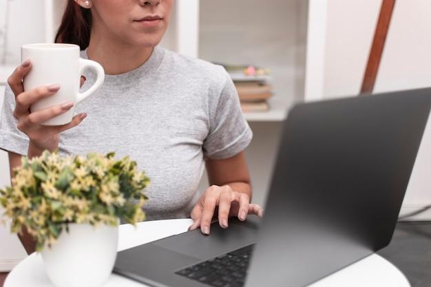 Vista frontal da mulher trabalhando no laptop, mantendo a caneca