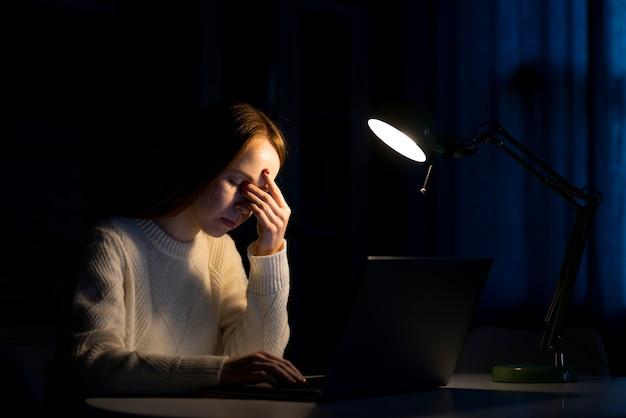 Vista frontal da mulher trabalhando no laptop