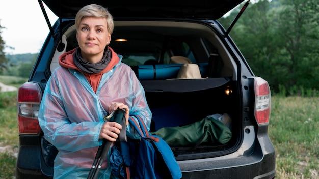 Vista frontal da mulher turista sênior ao lado do carro