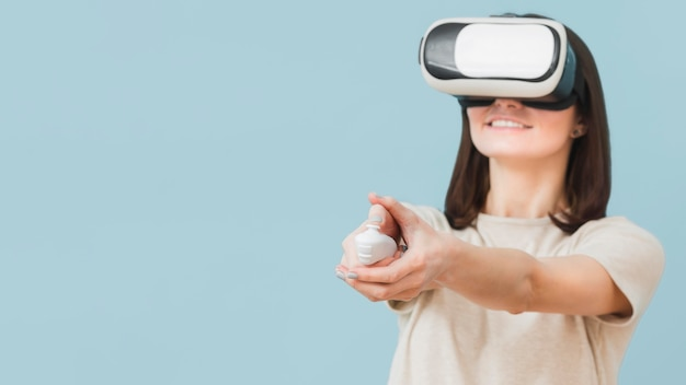 Vista frontal da mulher usando fone de ouvido de realidade virtual e se divertindo