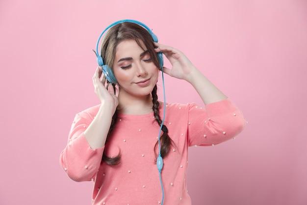 Vista frontal da mulher usando fones de ouvido, curtindo música