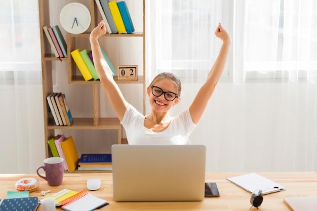 Vista frontal da mulher vitoriosa trabalhando no laptop em casa