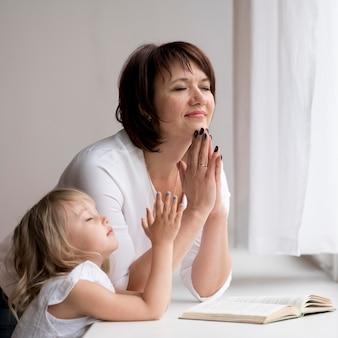 Vista frontal da neta e avó rezando
