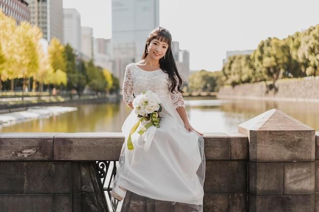 Vista frontal da noiva com buquê de flores posando à beira do rio