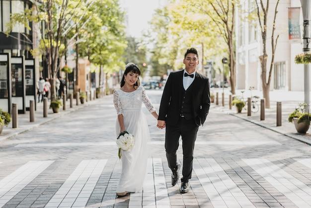 Vista frontal da noiva e do noivo caminhando na rua