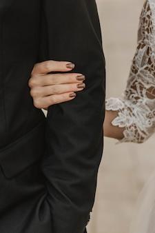 Vista frontal da noiva segurando o braço do noivo