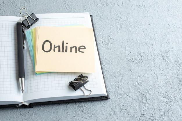 Vista frontal da nota escrita on-line com caneta e bloco de notas no fundo branco