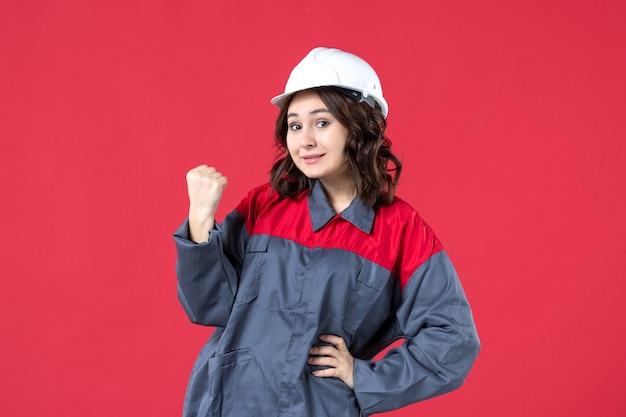 Vista frontal da orgulhosa construtora de uniforme com capacete em fundo vermelho isolado