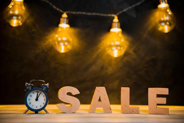 Vista frontal da palavra venda e lâmpadas com mesa de madeira