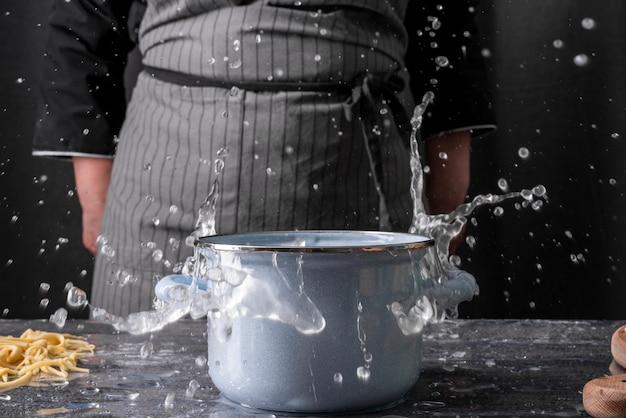 Vista frontal da panela com água e chef