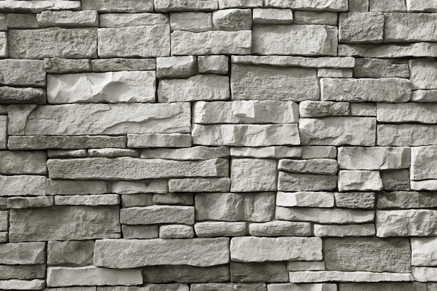 Vista frontal da parede de pedra áspera cinza monótona para fundo de textura