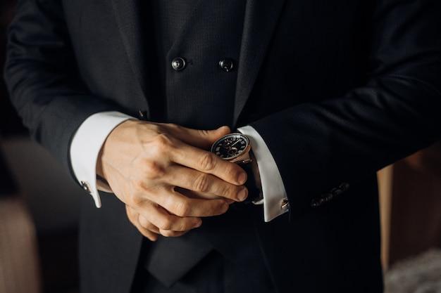 Vista frontal da parte do peito de um homem vestido de terno preto elegante e relógio precioso, mãos de homem