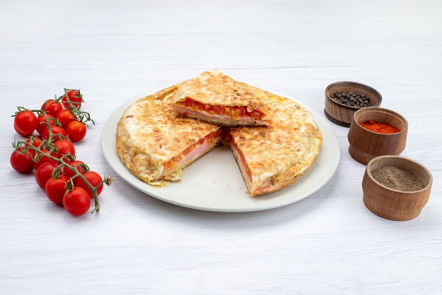 Vista frontal da pastelaria vegetal cozida dentro de chapa branca com tomates vermelhos frescos na superfície branca