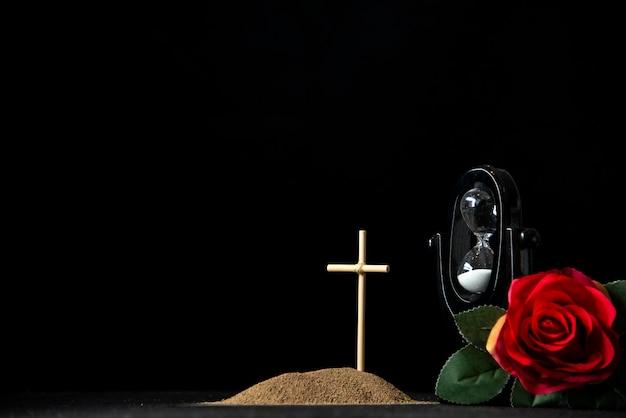 Vista frontal da pequena sepultura com ampulheta e rosa vermelha em preto