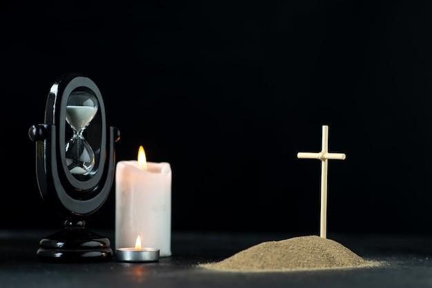 Vista frontal da pequena sepultura com ampulheta e velas no escuro
