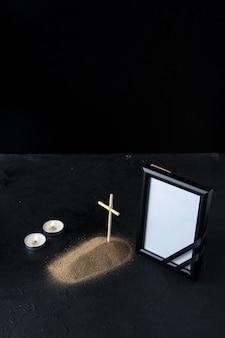 Vista frontal da pequena sepultura com cruz e moldura no escuro