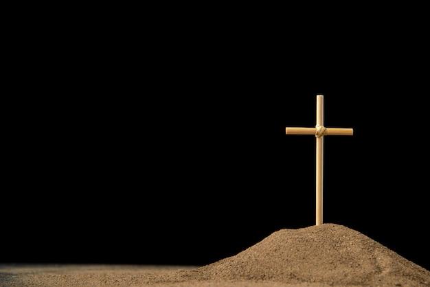 Vista frontal da pequena sepultura com cruz no escuro