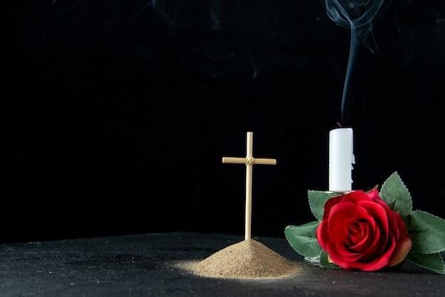 Vista frontal da pequena sepultura com flor e vela no escuro