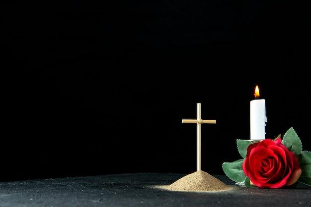 Vista frontal da pequena sepultura com flor vermelha em preto