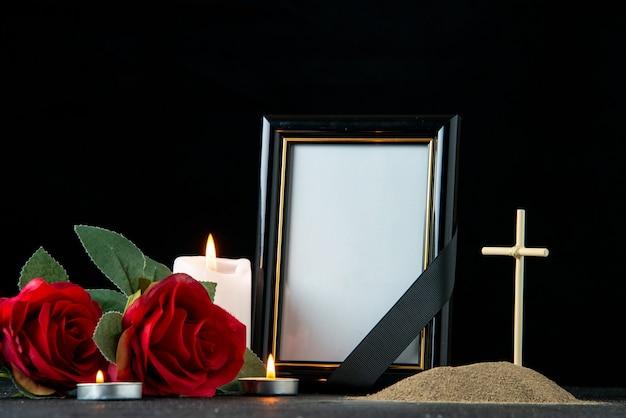 Vista frontal da pequena sepultura com flores e velas no escuro