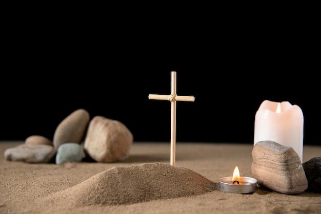 Vista frontal da pequena sepultura com pedras na areia