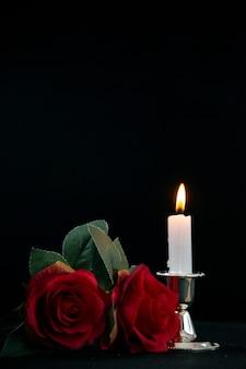 Vista frontal da pequena sepultura com uma vela acesa no preto